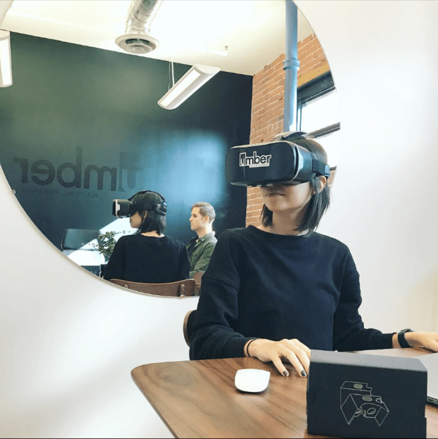 A woman sits at a table while using a VR headset